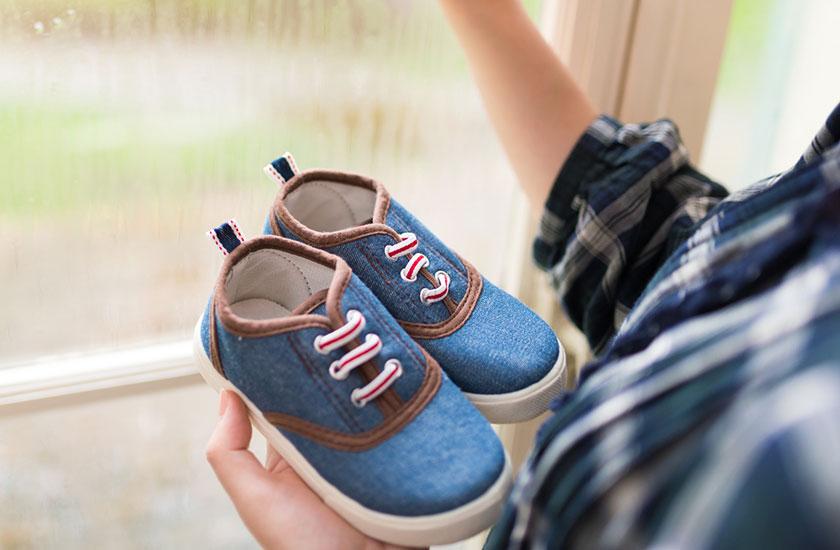 子供の靴を掌にのせた母親