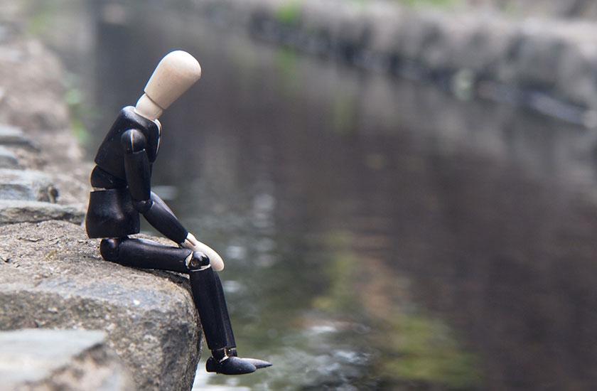 川岸に座る男性の人形