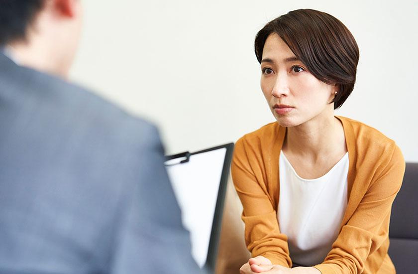 探偵事務所で調査について説明をうける女性