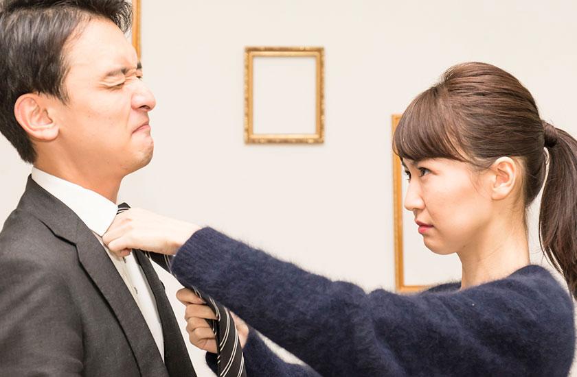夫のネクタイをきつく結ぶ妻