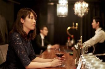 バーカウンターで1人ワインを飲む既婚女性
