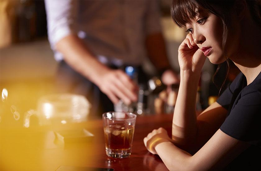 バーカウンターで寂しそうにしている女性