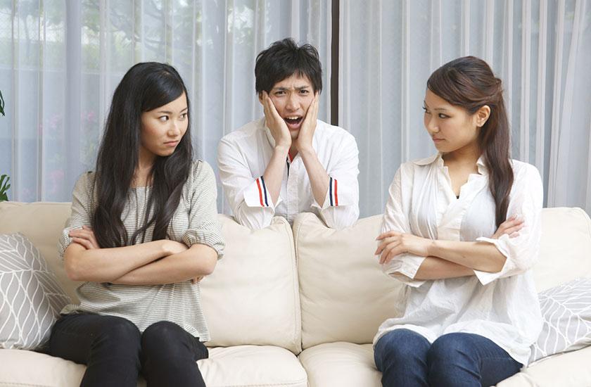 夫の浮気相手を睨み付ける女性とオドオドする夫