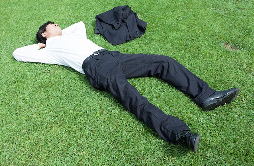 公園でサボって昼寝するサラリーマン