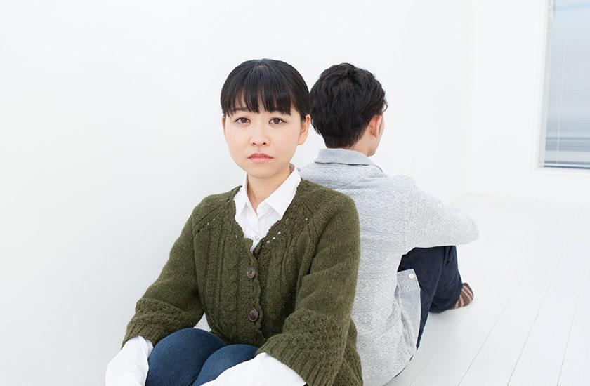 お互いに背をむけて座るカップル