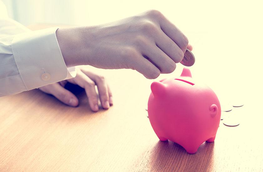 貯金箱に貯金する女性