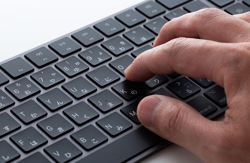 パソコンのキーボードと男性の手