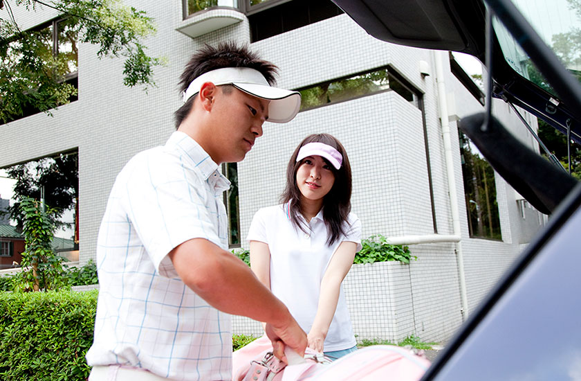 女性のゴルフ道具を車に積み込む男性