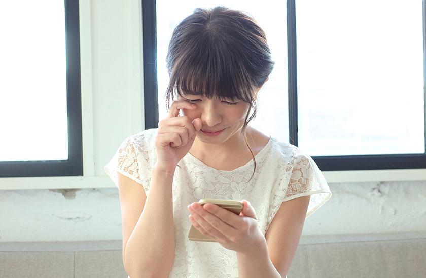 スマートフォン片手に涙する女性