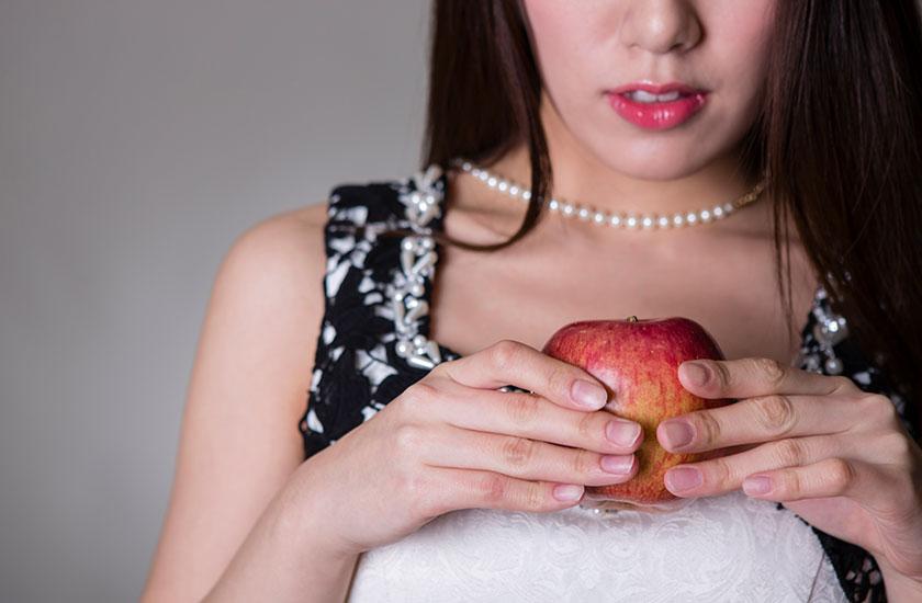 禁断の果実を手に持つ女性