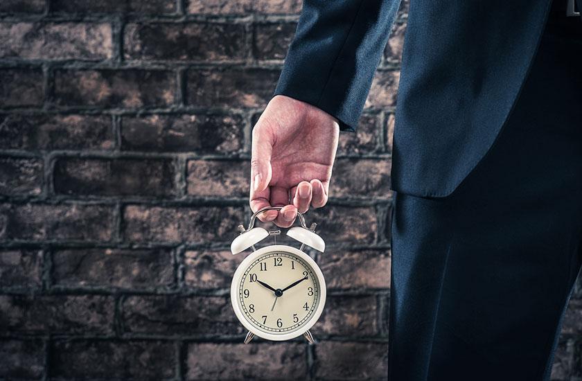 目覚まし時計を片手に持つ男性