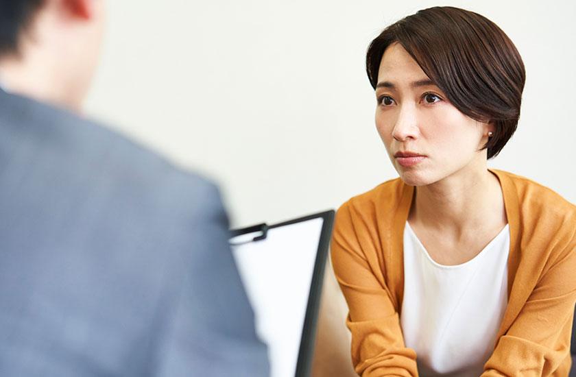 探偵事務所でパートナーの浮気調査の相談をする女性