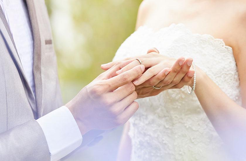 妻の指に結婚指輪をはめる夫