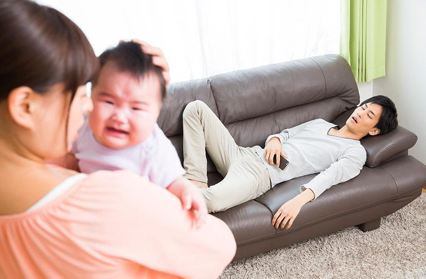 休日に寝てばかりいる夫と赤ちゃんを抱き抱える妻