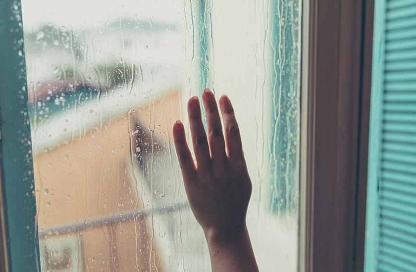 雨の日の窓と女性の手