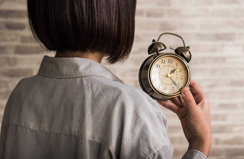 目覚まし時計と女性