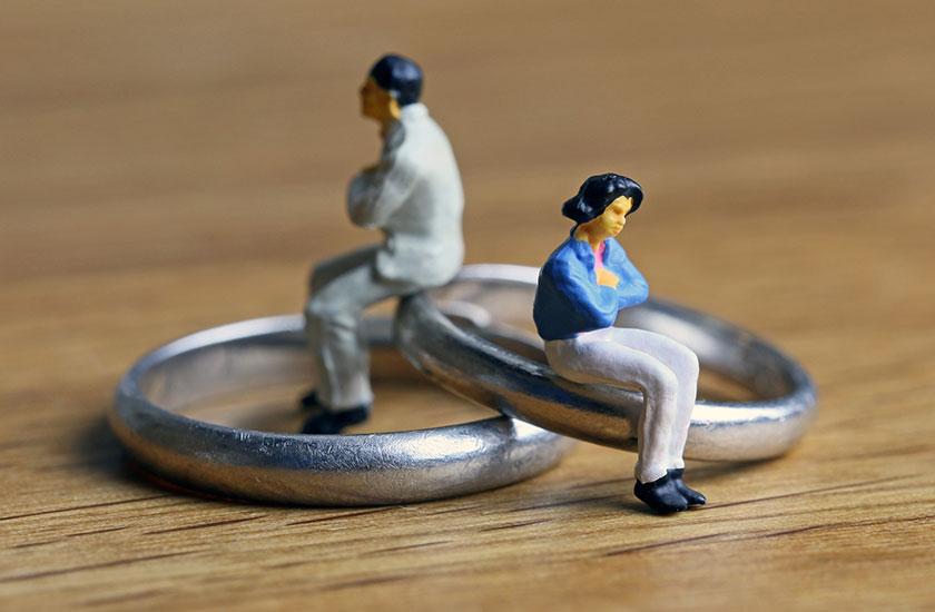 結婚指輪に腰掛ける夫婦の人形