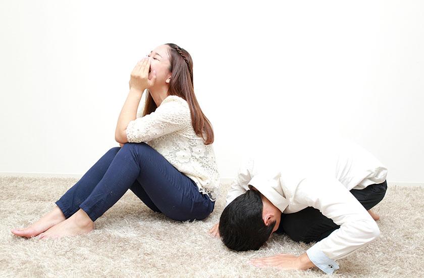 土下座するパートナーを見て思わず笑う女性