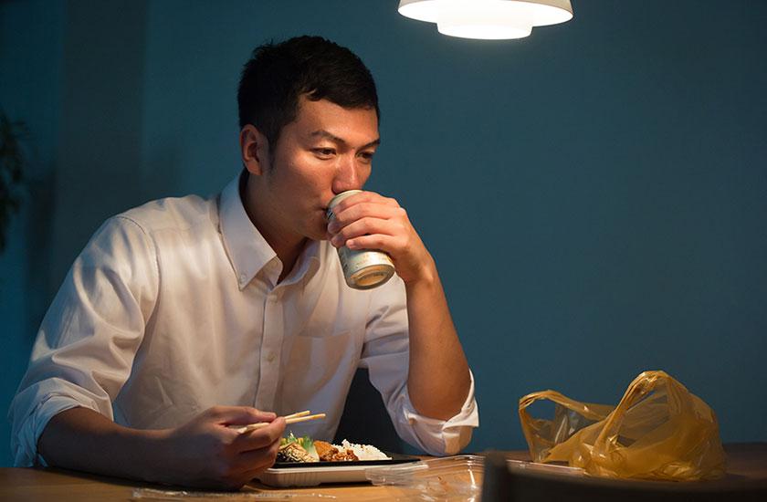 単身赴任先で寂しく夕食を食べる男性