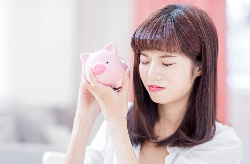 貯金箱と高額費用に悩む女性