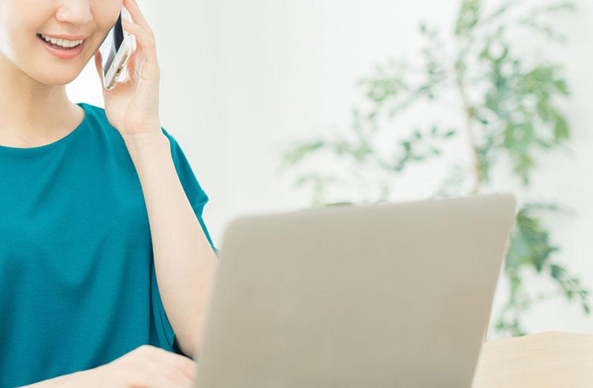 ノートパソコンと電話でカウンセラーに相談する女性