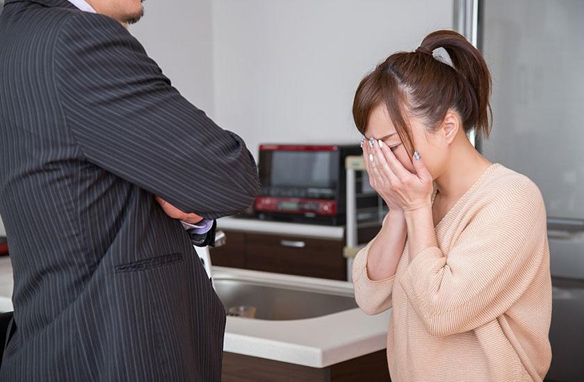 夫の前で泣く女性