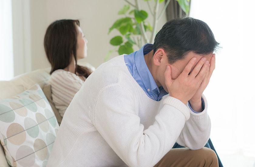 夫婦喧嘩をして頭を抱える40代男性