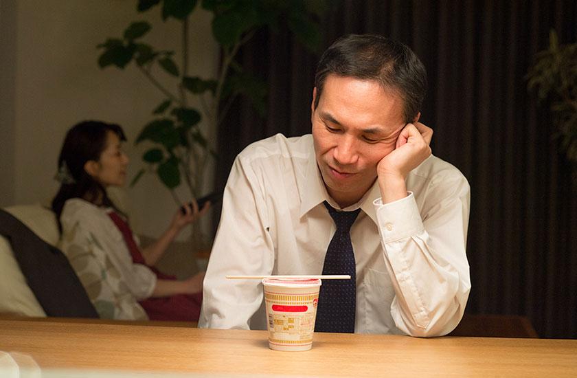 一人で寂しく夕食を食べる男性
