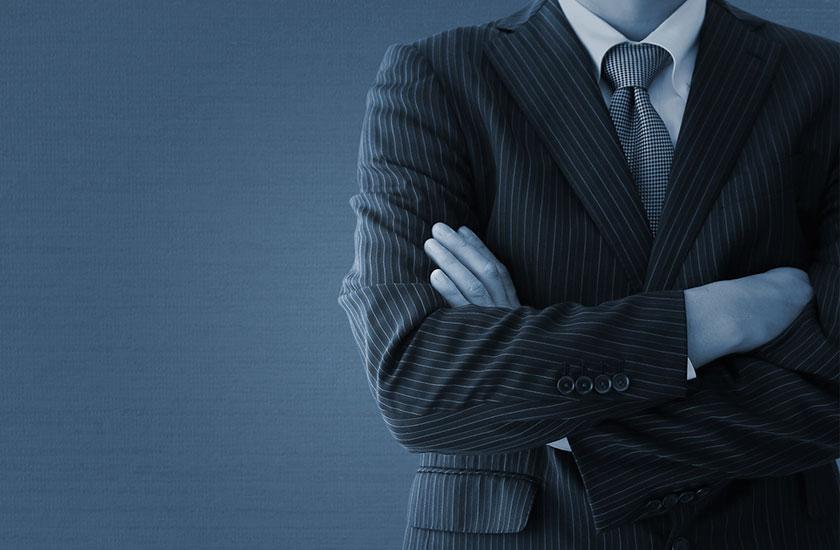 腕を組むスーツ姿の男性