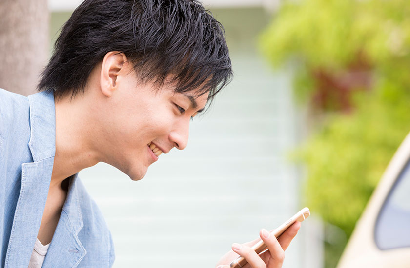 携帯電話で浮気相手を連絡をとる既婚男性