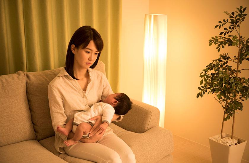 赤ちゃんを抱きかかえながら夫の帰りを待つ妻