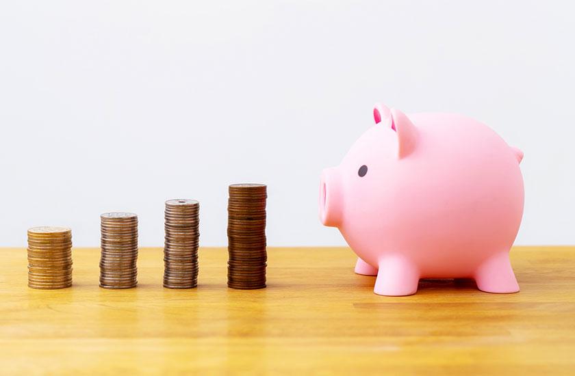 積み上がったコインと豚の貯金箱